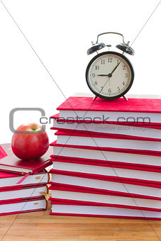 alarm clock and books on a table