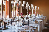 Decorated tables with candelabra at wedding reception, selective