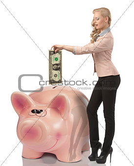 business woman saving one dollar in a pink bank