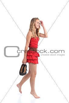 Teen girl wearing dress walking with heels hanging from her hand