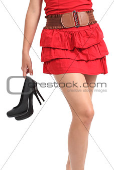 Close up of a woman walking carrying the heels in her hand