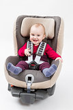 happy child in booster seat for a car in light background