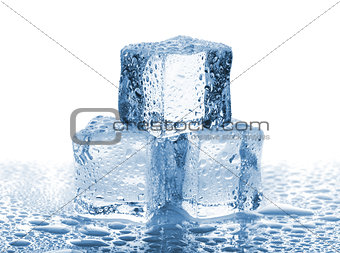 Three ice cubes with water drops