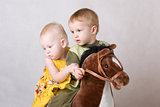 two children playing with a toy horse