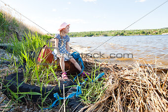 small girl on the bank of river with rubbish