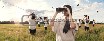 Multiplied girl looking with binoculars