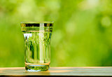 Glass Full of Water against the Green Nature Background