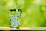 Pouring Water into a Glass against the Green Nature Background