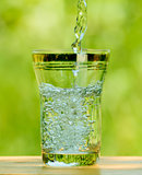 Pouring Water into a Glass against the Green Background