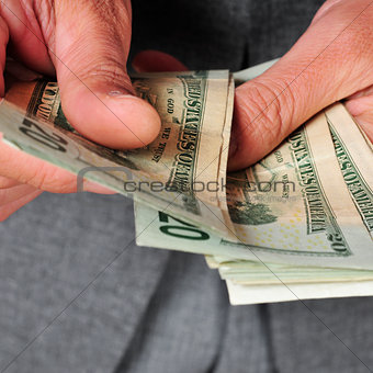 man in suit with counting dollar bills