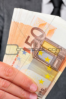 man in suit with a wad of euro bills