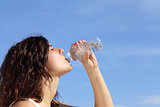Profile of a woman drinking water from a plastic bottle