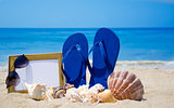 Flip-flops with photoframe and seashells on sandy beach