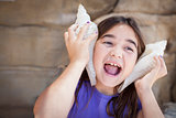 Young Girl Playing with Large Sea Shells Against Her Ears