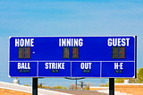 Baseball scoreboard with blue sky