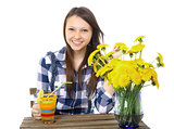 Girl teenager, caucasian appearance, brunette, wearing a plaid shirt, holding a glass of drink. On the table is a blue vase,  with a bouquet of yellow wildflowers, dandelions.