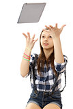 The girl throws in the air tablet PC .  Teenage girl in a plaid shirt and short denim shorts, tosses a PC tablet to the top.