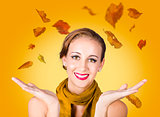 Elegant female model catching autumn leaves