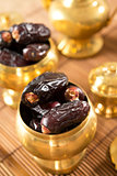 dried date fruits in golden metal bowl.