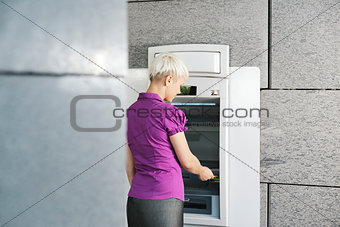 young woman withdrawing money with card at atm