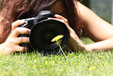 Close up of a pretty girl taking a photograph of a flower on the grass