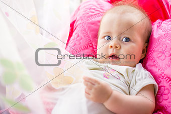 baby lying on a pink pillow