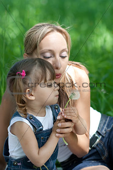Mother and daughter in jeans with dandelion outdoor
