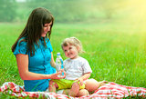 mother and daughter have picnic outdoor drinking water from plas