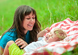 happy mother and daughter have picnic outdoor on green grass