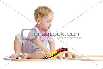 Cute child is playing with wooden train isolated on white