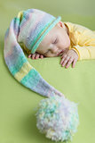 sleeping baby in funny hat on green background