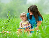 mother and daughter reading book together  outdoor