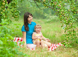 mother and daughter have picnic outdoor under apple tree branch