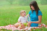 mother and daughter have picnic drinking clear water from bottle