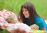 mother and daughter lying together in grass and looking each oth