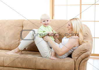 Happy son and mother playing on sofa