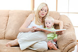 Son and mother sitting on sofa and reading book together