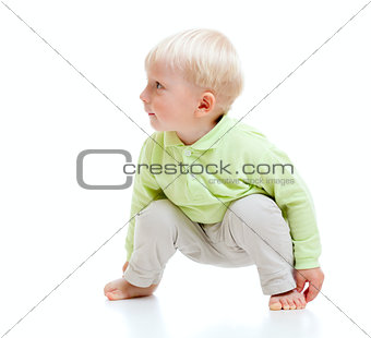 Blond boy barefooted sitting at floor and looking right isolated
