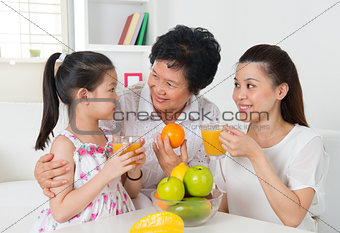Asian family drinking orange juice.