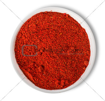 Ground paprika in plate isolated
