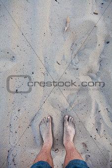 Men's barefoot feet in the sand