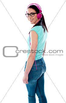 Attractive girl wearing headphones looking back