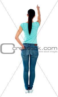 Rear view of young woman in casuals, pointing