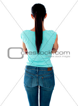 Beautiful young woman looking at wall. Rear view