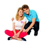 Teenage couple sitting on floor, studio shot