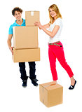 Young couple holding and moving boxes