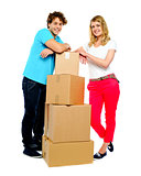 Teenager couple posing beside cardboard boxes
