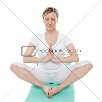 Blonde lady meditating in white