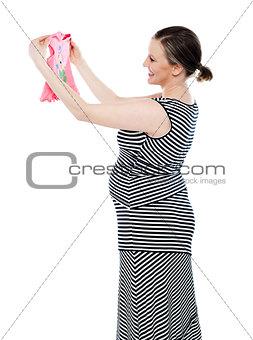 Pregnant woman looking at baby cloth, rejoicing