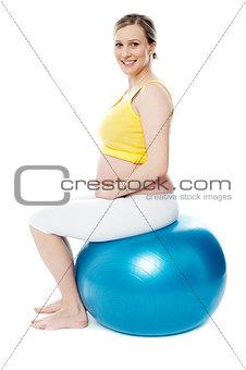 Pregnant woman sitting on gymnastic ball